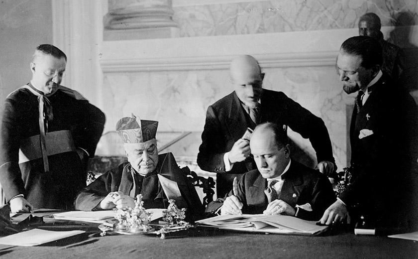 Кардинал Ґаспарі та Беніто Муссоліні підписують Латеранські угоди